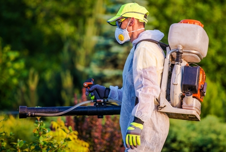 Garden Pest Control Services. Men with Gasoline Pest Control Spraying Equipment. Professional Gardening Stock Photo