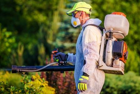 riesgo quimico: Jardín Servicios de control de plagas. Los hombres con gasolina Pest Control de equipos de pulverización. jardinería profesional Foto de archivo