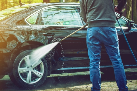 soaping: Men Cleaning His Modern Car. Outdoor Car Washing by High Pressured Water Stock Photo