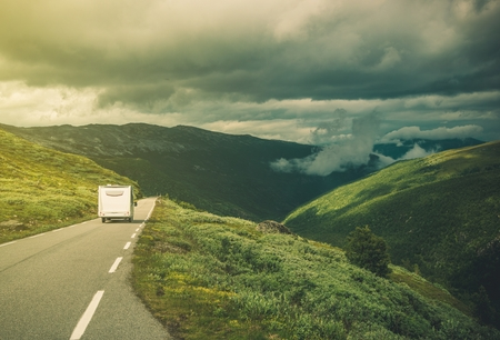 Traveling in RV Camper Van. Class C Camper on the Mountain Road. Stock Photo