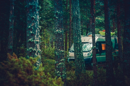 motorcoach: RV Forest Camping. Motorcoach RV Class B Boondocking in Forest. Camper Van Camping. Stock Photo