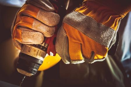 working hands: Construction Worker with His Screw Gun Closeup Photo