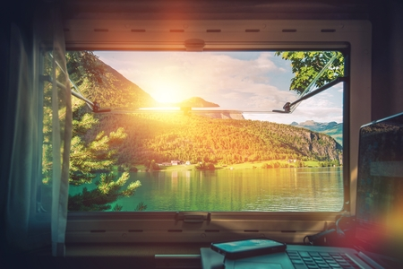 motorcoach: Work Desk with Scenic View. Working in the Camper Van Motorhome While Traveling During Vacation Time. Working on Laptop Inside RV Motorcoach. Stock Photo