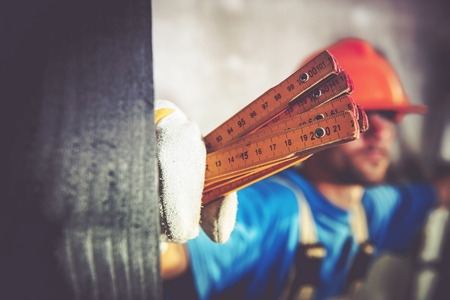 wood turning: Construction Worker with Measuring Tool Closeup Photo. Home Construction Site Theme.