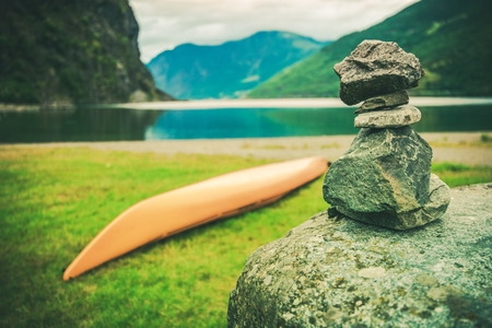 cairn: Destination Norway Cairn. Norwegian Fjord, Kayak and Pile of Stones Left by Tourist.
