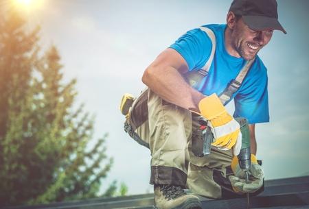 Gelukkig bouwvakker lachend tijdens het werken op Houten Dak. Tevreden Worker. Stockfoto