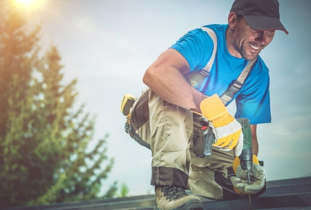 Happy Construction Worker Smiling While Working on Wooden Roof. Satisfied Worker. Standard-Bild