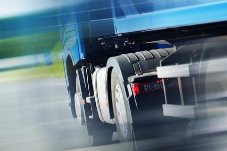 Semi Truck Spedition. Speeding Semi Truck on the Highway. Closeup Photo. Heavy Duty Transportation. Stock Photo