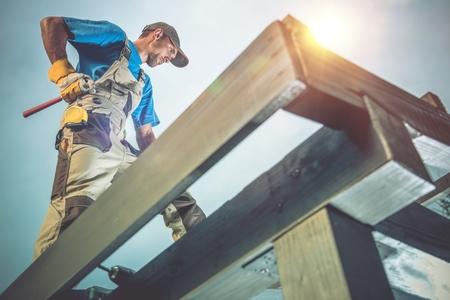 Houten bouwwerken. Kaukasische Arbeider op de houten dakconstructie.