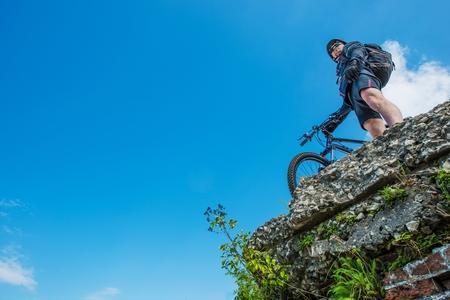 Ultimate Bike Riding Concept Photo. Caucasian Sportsman Biker on the Edge of Urban Ruins on His Mountain Bike.