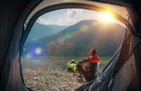 Tenting and Kayaking on the Lake. Caucasian Sportsman Camping and Kayaking on the Scenic Mountain Lake Shore.