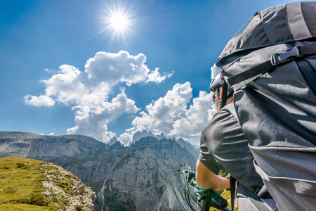 Mountain Bike Trip. Caucasian Sportsman with Backpack on His Bike in the High Mountain Landscape During Sunny Summer Day. Banco de Imagens