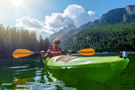 Caucasian Sportsman Kayaking on the Scenic Lake. Italian Dolomites, Lake Misurina, Europe. Banco de Imagens