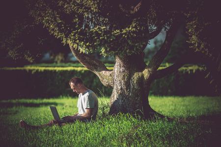 Internet Break Under the Tree. Men Enjoying Wireless Internet Connectivity. WiFi Connection in the Garden. Caucasian Men Working Remotely on His Laptop Computer. Stok Fotoğraf