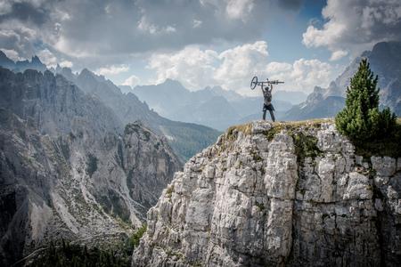 Mountain Biker Winning Concept. Zdeterminowany kaukaska Biker Obchody osiągnięcie na szczycie góry. Kolarstwo Concept.