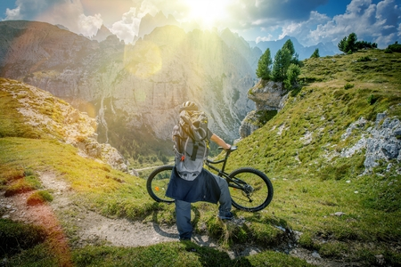 Mountain Trail Biking. Scenic Place in the Mountains. Caucasian Biker Taking Moment to Enjoy the View. Italian Dolomites. Stock Photo