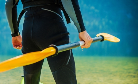 Kayaker in Wetsuit with Straight Paddle Closeup Preparing For Kayak Tour.