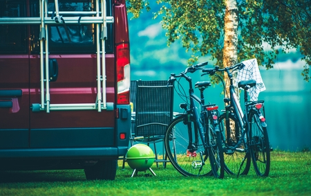 motorcoach: RV Camper Camping and Biking. Motorcoach and Two Bikes on the Campsite.