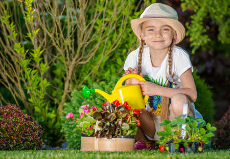 Caucasian Girl Taking Care of the Garden. Watering Flowers.