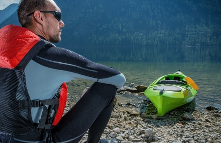 Kayaker and the Lake. Caucasian Kayaker in His 30s Resting on the Lake Shore After Long Kayak Trip. Reklamní fotografie