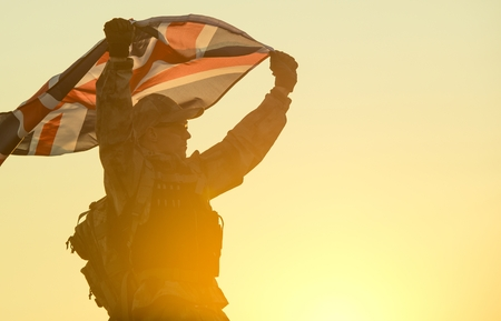 uk: British Soldier with UK Flag in His Hands. Military Concept.