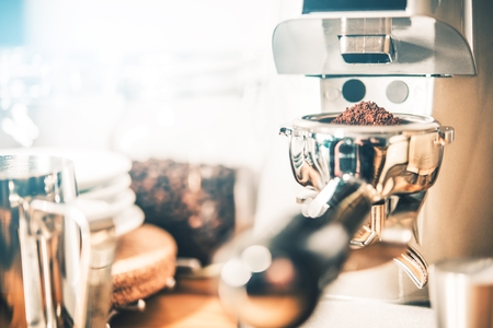 grinded: Espresso Coffee Grinding in Professional Coffee Grinder. Portafilter Loaded with Freshly Grinded Coffee. Stock Photo