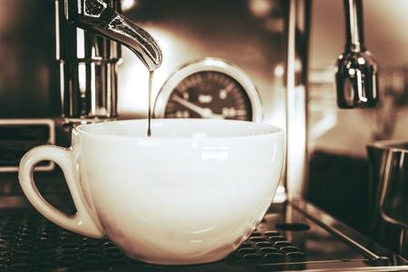 Cappuccino in the Making. Coffee Cup Under Coffee Machine Portafilter. Making Espresso Shot.