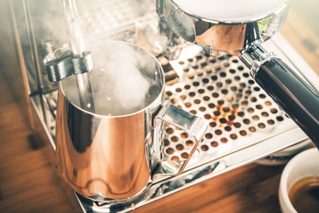 steaming: Steaming Milk For Cappuccino Coffee. Steaming Milk in Metal Steaming Pitcher Stock Photo