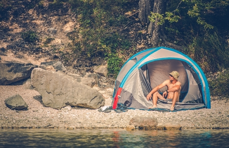 Tent Camping on the Rocky Lake Shore. Outdoor Men Lifestyle. Stock Photo