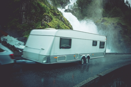 Travel Trailer Vacation Trip. Caravaning on the Road. Speeding Car with Travel Trailer on the Norway Scenic Road.