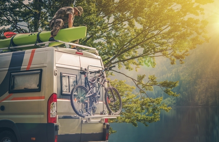 attaching: Ultimate RV Escape. Outdoor Men and His Camper Motorhome. Men Attaching His Kayak on the Camper Roof.