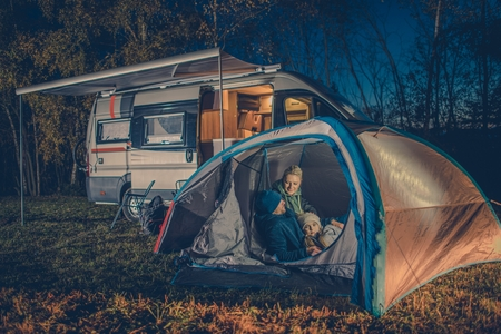 motorcoach: Caucasian Family Camping Fun. Caucasian Family in the Tent. RV Motorhome Camper in the Background. Stock Photo