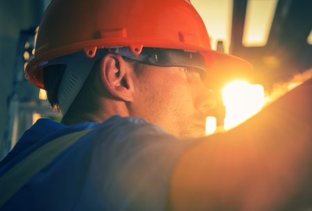 Construction Worker in the Sun. Caucasian Worker in His 30s Wearing Red Safety Helmet.