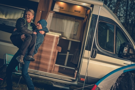 Happy Couples and the RV. Young Couples on the Campground with Their Motorhome Enjoying New Purchase.
