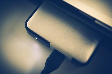 secure: Small Portable Hard Drive Closeup Photo. Bluish Color Grading.