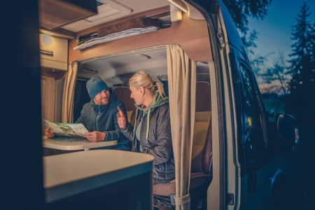 커플과 캠핑카 캠핑. 젊은 커플은 캠프에서 다음 여행을 계획하고 있습니다.