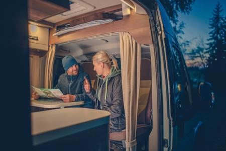 Paare und der RV Park Campingplatz. Junge Paare Planung nächste Reise im Wohnmobil.
