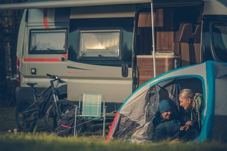persona viajando: Las parejas románticas tienda de campaña. Las parejas jóvenes de raza caucásica se divierten dentro de su tienda de campaña en el camping.