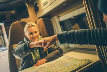 recreational: Approved RV Trip Fist Bump. Happy Couples in the Camper Motorhome Planning New Road For the Next Day Trip.