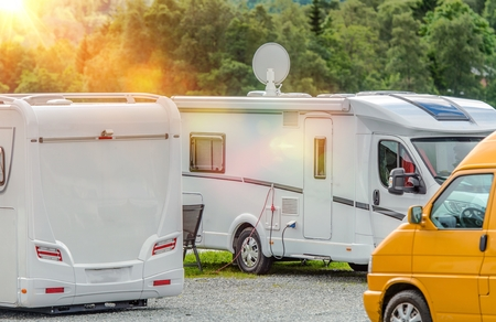 motorcoach: RV Park Campers. Few Motorhomes in the RV Park. Motorhome with Satellite TV Connection. Stock Photo