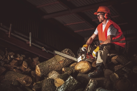 wood cutter: Wood Cutting Work. Caucasian Worker Resting on Pile of Chopped Firewood.  Stock Photo