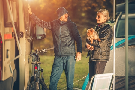 touring: Young Caucasian Couples with Dog Motorhome RV Camping. Campground Fun.