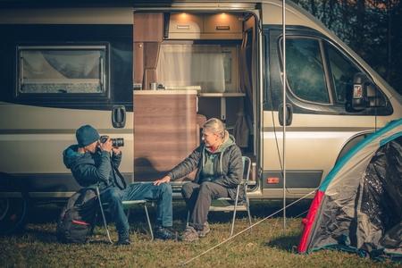 ヤング カップル キャンプ場に楽しい時を過します。RV キャンピングカー キャンプします。デジタル カメラを使用して彼の妻の写真を撮る男性。