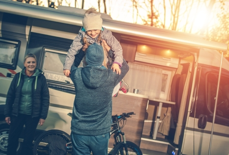 motorcoach: Family Camping Time. Young Family with Kid and Camper Motorhome During Autumn Camping Trip.