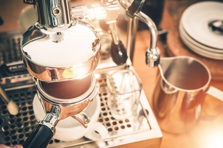 grinded: Manual Coffee Machines Espresso Making. Elegant Stainless Steel Coffee Machine and Portafilter Full of Fresh Arabica Coffee