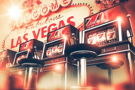 Slot Machine Games in Las Vegas Concept. Vegas Gambling 3D Render Illustration. Row of Slots Machines and Vegas Sign in the Background. Stock Photo