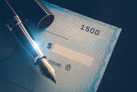 エレガントな万年筆を使用して書き込みチェックのお支払いします。エグゼクティブ デスク ビジネス コンセプトです。企業の給料。