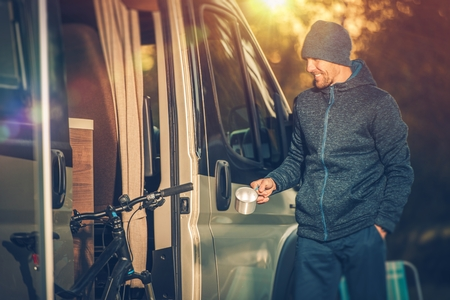 single: Satisfied Smiling Men with Small Cup of Coffee and His Camper Van Recreational Vehicle. RV and Mountain Bike Concept. Having Fun on the Camping.  Stock Photo