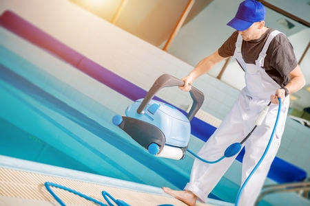 Swimming Pools Technician with Pool Cleaning Robot Preparing For Work. Caucasian Technician Cleaning Professional.