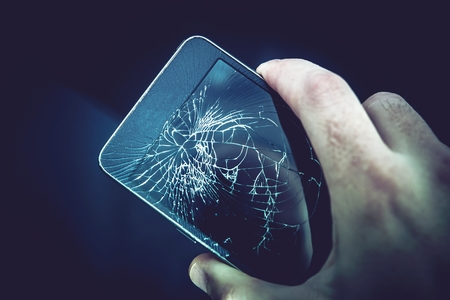 Damaged Smartphone Screen. Broken Mobile Phone in a Hand.